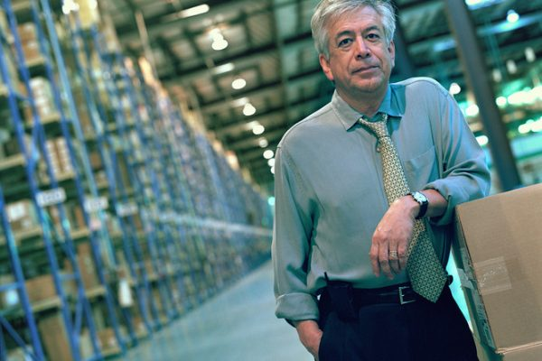Businessman leaning on stack of boxes in warehouse, portrait